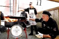 En la imagen se puede apreciar un cocinero avivando el fuego mientras que una cocinera remueve el caldo de la paella.