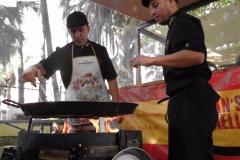 Momento del cocinado de la Paella. Se aprecia al cocinero con el delantal personalizado puesto